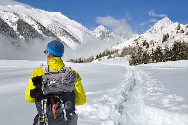 Path in the snow crossing alpine mountain
