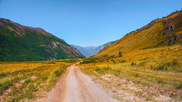 山を通る小道。トレッキング登山道。高地の草の間の未舗装の道路と明るいパノラマの高山の風景。上り坂の経路。山腹を上る。