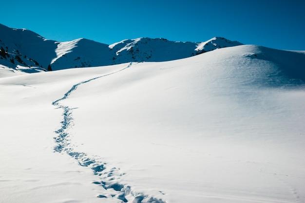 Тропа пути на зимнем восходе солнца, белом снежном поле на фоне замороженных гор.