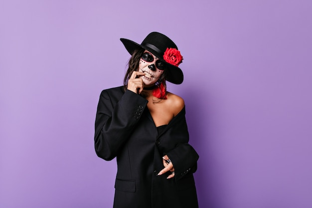Pathetic woman mafioso in black outfit touches her teeth and poses in skull mask on lilac isolated wall.