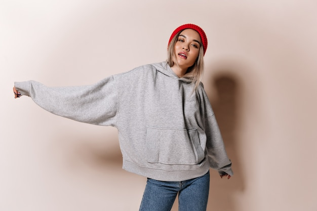 Pathetic woman in stylish street clothes posing on beige wall