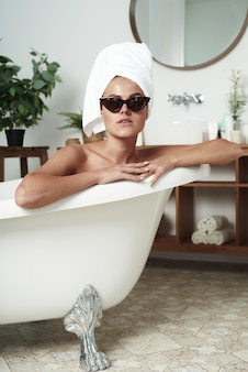The pathos beautiful girl with vitiligo lies in the bath in the cat's sunglasses and a towel on her head. the concept of fashion, skin care and style.