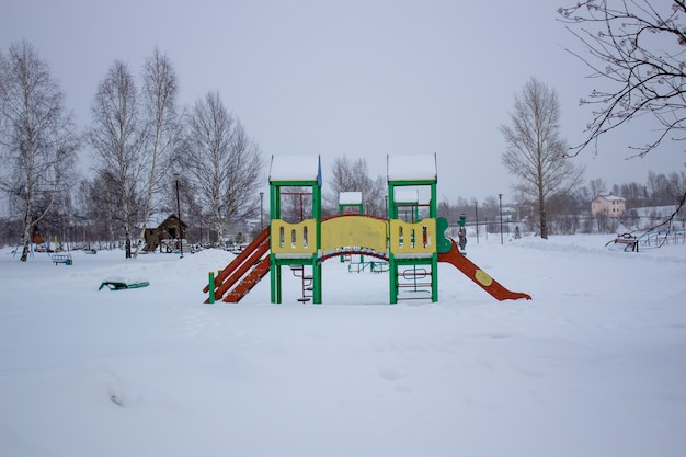 Paths in the winter park. bench, playground for children.