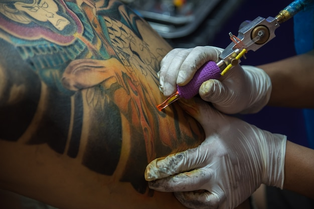 Pathumthani, thailand - may 6, 2017 : unidentified professional tattoo artist drawing art on body at