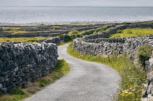 アイルランドの日光の下で岩と海に囲まれたイニシアーの小道