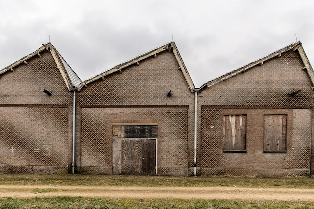 Pathway near a brick building with a cloudy sky in the
