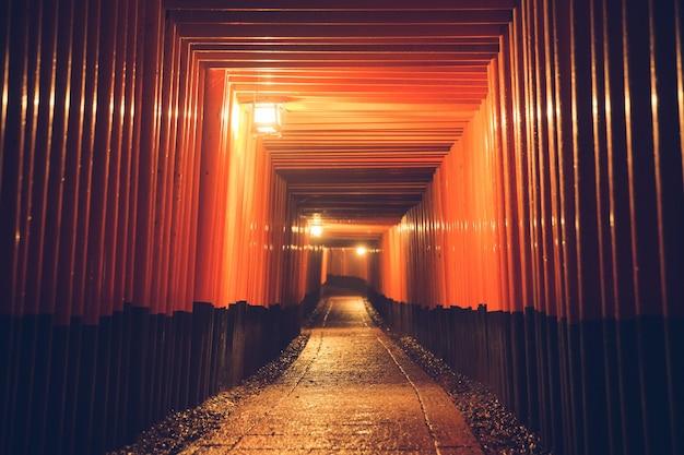 Pathway orii gates at fushimi inari shrine at night in kyoto, japan.