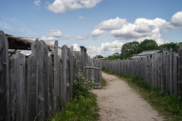 昼間は曇り空の下、木の塀と緑に囲まれた小道