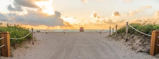 Путь к пляжу в майами-бич, флорида с океаном на рассвете