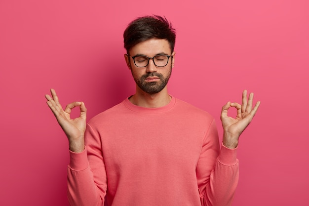 Patience, calmness and meditation concept. peaceful relieved bearded young man practices yoga exercise, keeps hands in zen gesture, closes eyes, poses over pink wall, controls his emotions