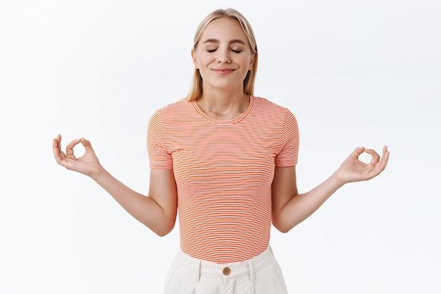 La pazienza è la chiave del successo. attraente donna caucasica bionda calma e sollevata in t-shirt a righe, chiudere gli occhi e sorridere raccogliendo relax, allargare le mani lateralmente fare segno mudra, meditare, praticare yoga
