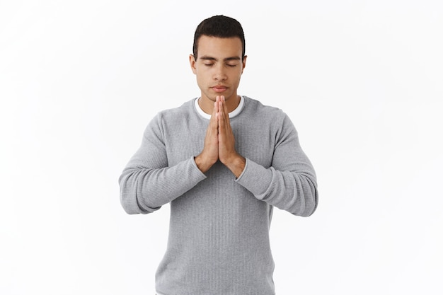 Patience and meditation concept. calm determined young hispanic man in sweater, praying god