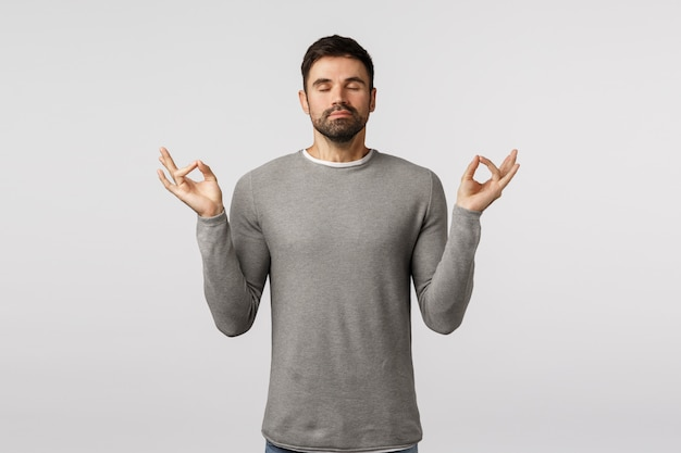 Patience, relaxation and meditation concept. peaceful young handsome bearded guy broaden mind and body, feeling zen, raise hands mudra gesture, practice breathing yoga with closed eyes