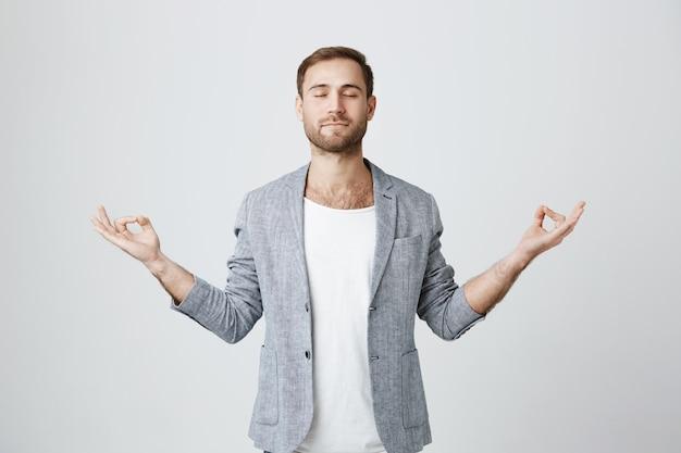 Терпеливый и спокойный бородатый парень медитирует с закрытыми глазами