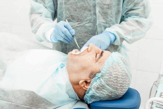Пациент и стоматолог во время установки имплантата. реальная операция. удаление зубов, имплантаты. здравоохранение оснащение врача рабочим местом. лечение зубов