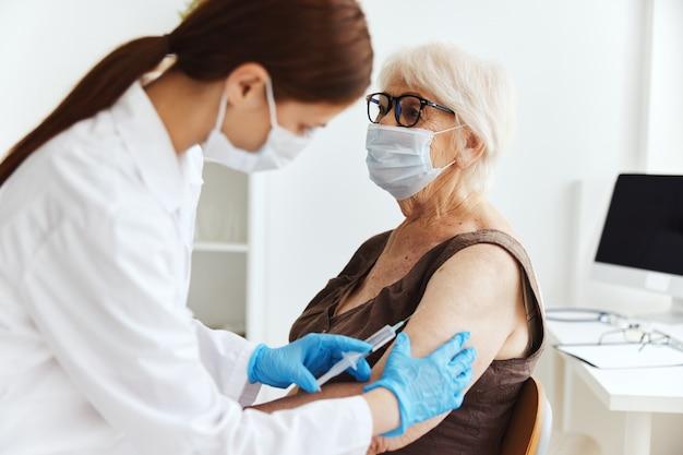 患者と医師の注射器注射ワクチンパスポートウイルスの流行