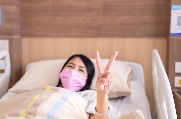 병원에서 아픈 침대에 2개의 손가락을 보여주는 환자 아시아 여성, 건강 보험 개념