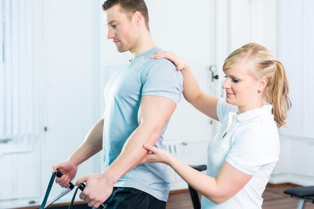 Пациент физиотерапевта делает физические упражнения с тросом боудена
