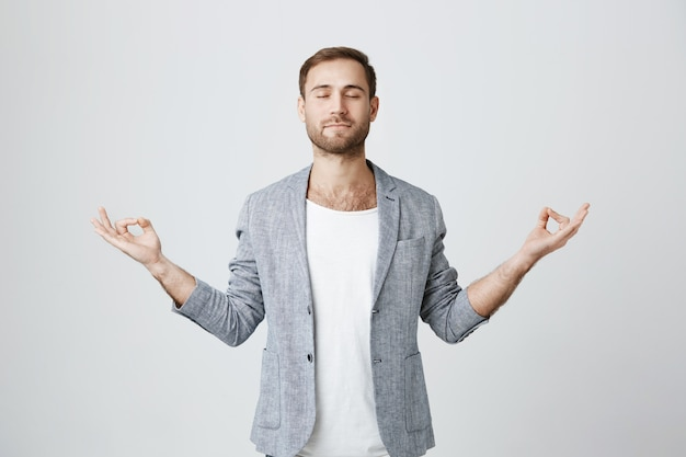 Patient and calm bearded guy meditating with closed eyes