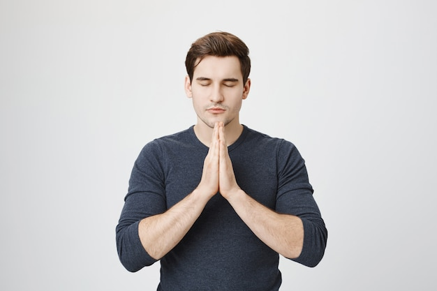 Patient calm handsome guy praying, hold hands in plead gesture