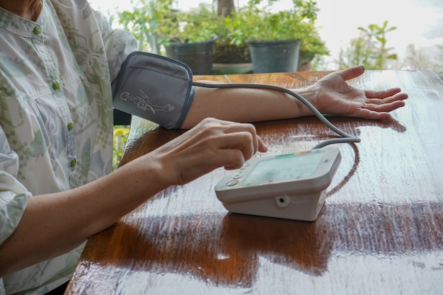 Patient checking up blood pressure using upper arm blood pressure measuring monitor
