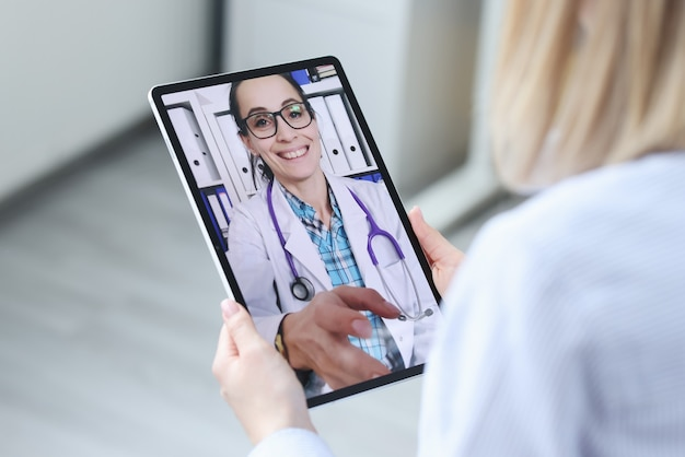 患者はタブレットのビデオ通話で医師に相談します。オンライン医療相談のコンセプト