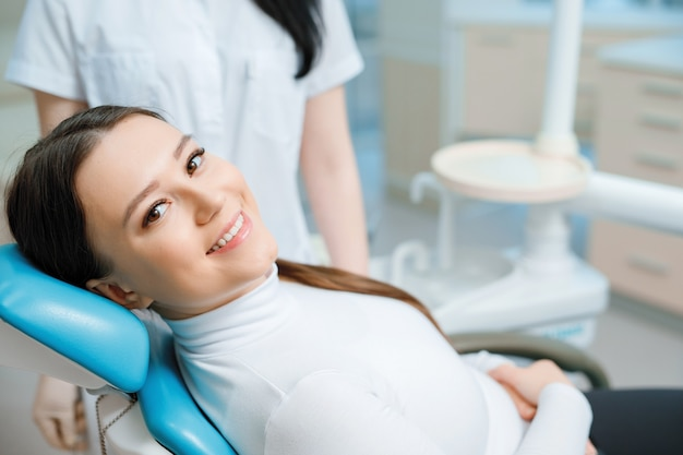 Patient in dental chair. beautiful young woman having dental treatment at dentist's office.