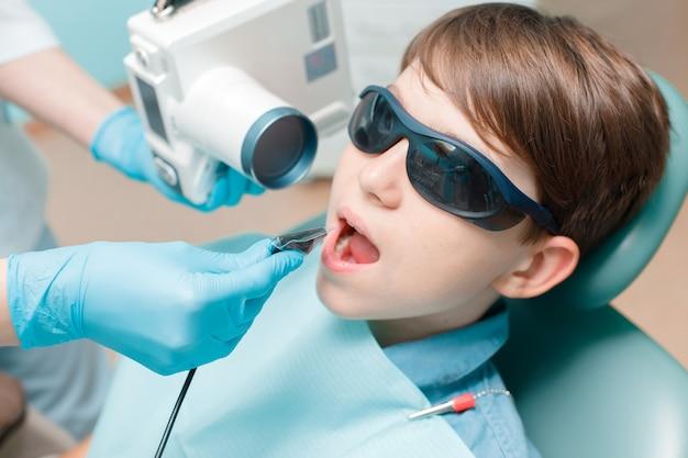 Patient in dental chair teen boy having dental treatment dentist takes jaw xray