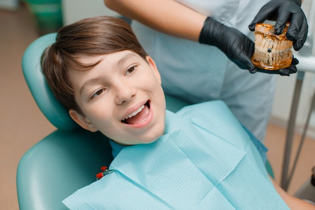 Patient in dental chair teen boy having dental treatment at dentists office