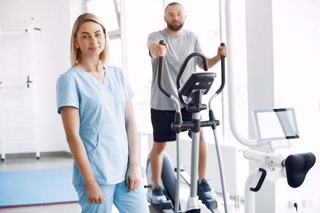 Пациент делает упражнения на велотренажере в тренажерном зале с терапевтом