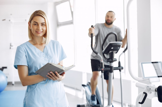 Patient doing exercise on spin bike in gym with therapist