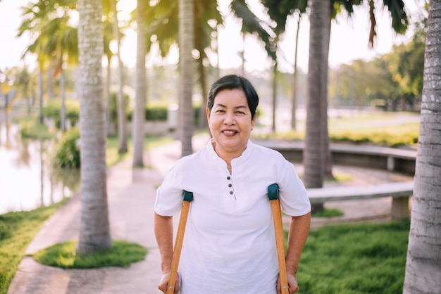 Patient elderly asian woman using crutches support broken legs for walking at public park,physical therapy concept