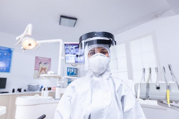 치과 진료실에서 코로나바이러스에 대한 안전 장비를 착용한 치과 의사의 환자 1인칭. 환자의 heatlhcare 검사 동안 covid에 대한 안전 장비를 착용하는 stomatolog.