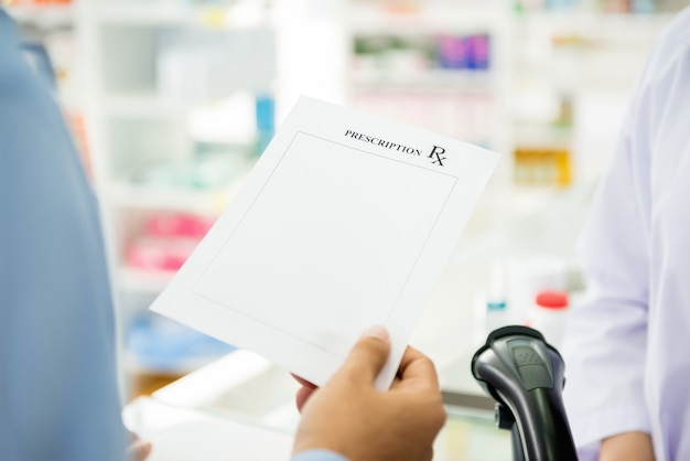 Patient giving rx prescription paper to pharmacist  in pharmacy