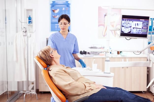 歯科医院の助手と口腔衛生について話し合っている患者。歯の問題について口腔病学オフィスの医療看護師と話している年配の女性。