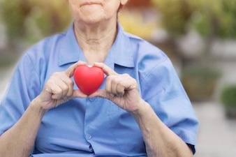 Patient holding heart in her hand, medical concept with healthy red love on age hand