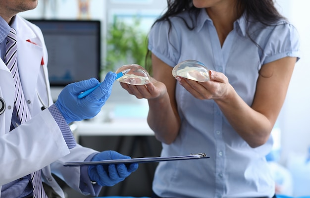 Patient holds breast implants next to doctor