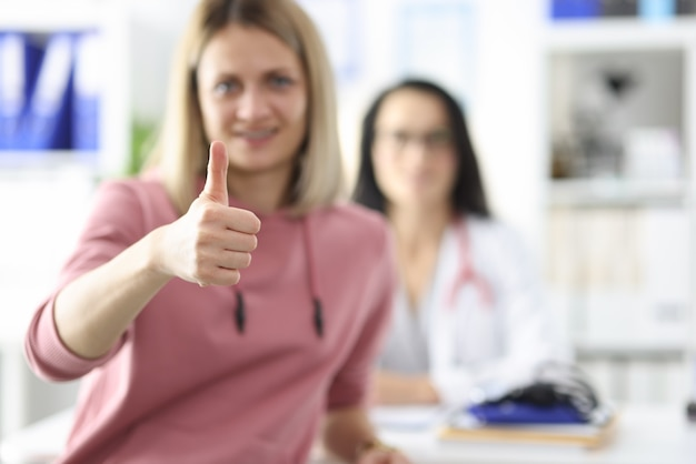 Patient holds thumb up in medical office doctor sits medical checkup for