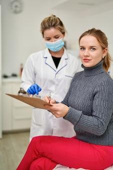 Пациент в эстетической клинике подписывает документ