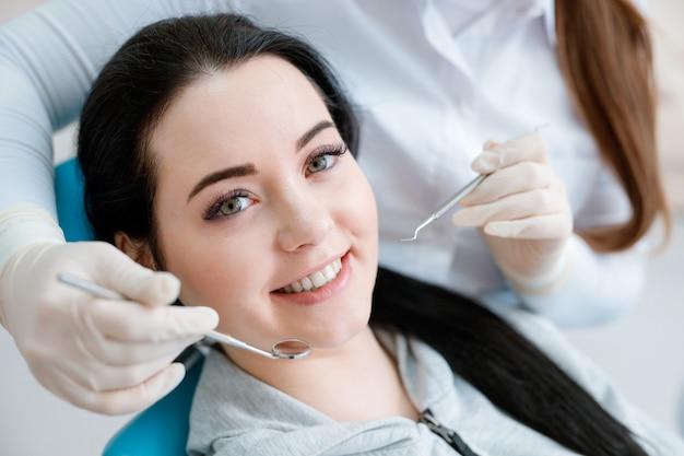 Пациент в стоматологическом кресле. красивая молодая женщина, имеющая стоматологическое лечение в офисе стоматолога.