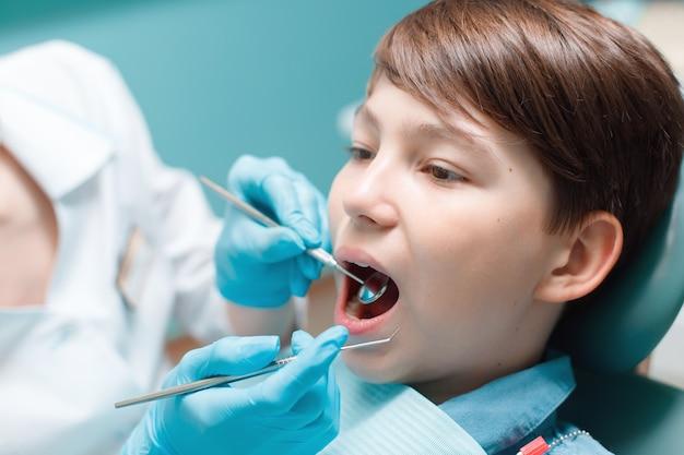 Пациент в стоматологическом кресле. мальчик-подросток, имеющий стоматологическое лечение в кабинете стоматолога.