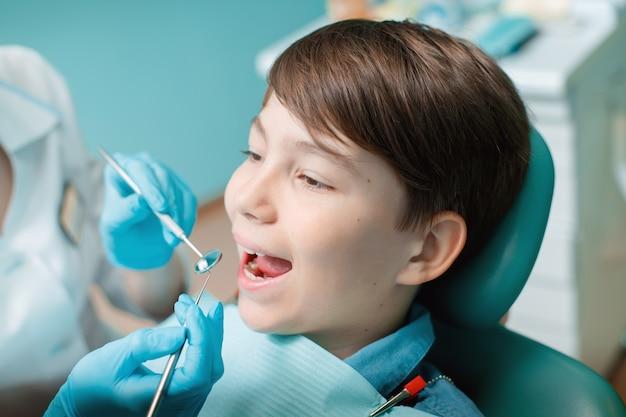 Пациент в стоматологическом кресле мальчик-подросток, имеющий стоматологическое лечение в офисе стоматолога
