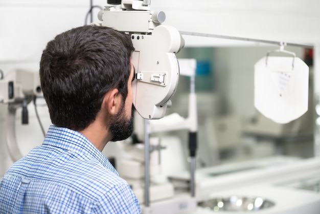 Patient is reading the optometrist chart in modern ophthalmology clinic.