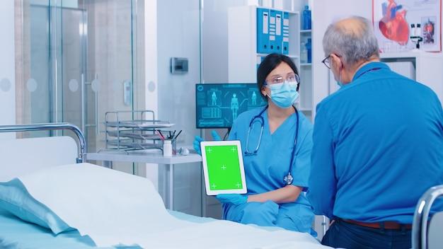 현대적인 개인 병원이나 진료소에서 녹색 화면 디지털 태블릿을 보고 있는 환자. 앱, 텍스트, 비디오 또는 디지털 자산에 대한 가젯의 격리된 모형 크로마 교체 화면입니다. 쉬운 키잉 메딕