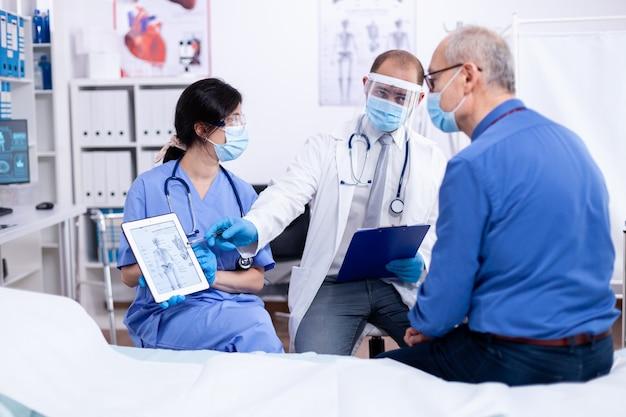 Пациент смотрит на рентгенографию своего скелета во время консультации с врачом в больнице, одетый в защиту от covid-19
