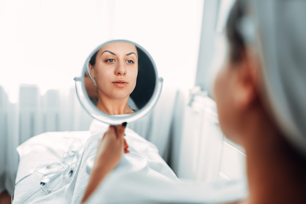 患者は鏡を通して自分の顔を見る