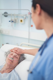 Patient lying on a bed closes her eyes in hospital ward