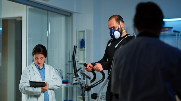 スポーツ科学研究室での運動中に心電図を作成し、持久力と心拍数を監視し、コンピューターにekgデータを表示している患者。マスクと医療用電極で走っている男