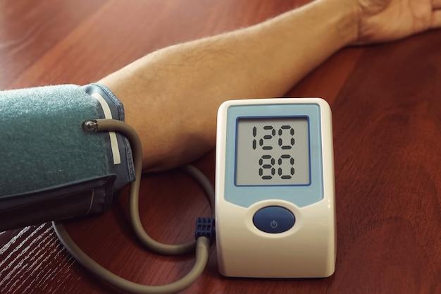 혈압을 측정하는 환자. 나무 탁자의 배경에 가해지는 압력을 측정하는 장치가 있는 남자의 손. 정상 혈압. 건강한 사람.