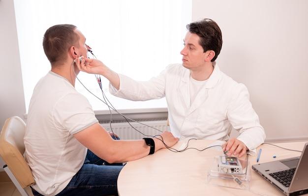 Тестирование нервов пациента с помощью электромиографии в медицинском центре
